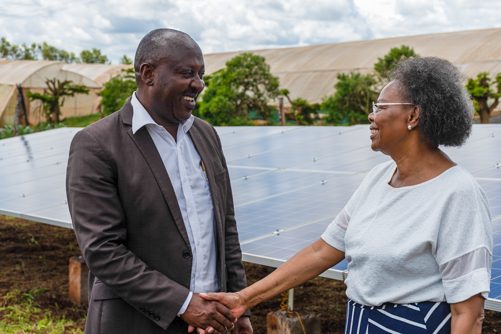 A man and a woman shake hands. In the background greenhouses and several solar panels.